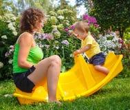 Moederzitting met haar zoon op babyschommeling Royalty-vrije Stock Afbeeldingen