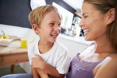 Moederzitting met Lachende Zoon bij Ontbijtlijst stock foto's