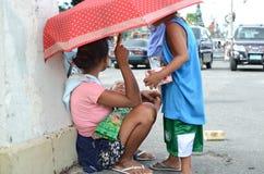 Moederzitting op bestrating met siblings die zoon van de paraplu de knuffelende baby gebruiken bij kerkwerf Stock Foto
