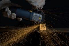 Moedor de ângulo que corta um tubo do quadrado do metal que faz o chuveiro da faísca Fotografia de Stock Royalty Free