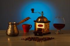Moedor de café, cezve, copo, feijões de café com vidro de aguardente Fotografia de Stock Royalty Free