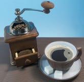 Moedor de café com a xícara de café no fundo azul Fotografia de Stock