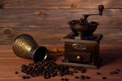 Moedor de café do vintage, potenciômetro do café do turco e feijões de café de cobre no fundo de madeira marrom foto de stock royalty free