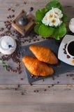 Moedor de café, dois croissant amanteigado francês e copo do café do aroma no fundo de madeira Fotografia de Stock Royalty Free