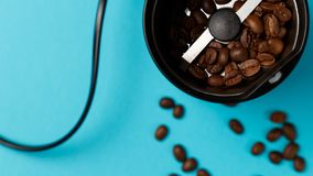 Moedor de café elétrico com os feijões de café roasted na cozinha fotografia de stock