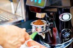 Moedor de café que mói feijões de café recentemente roasted em um coff Fotografia de Stock Royalty Free