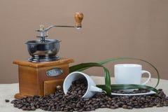 Moedor e copos de café em algum feijão Fotos de Stock Royalty Free