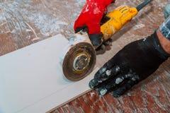 moedor lateral que trabalha em pavimentar a telha no terreno de construção imagens de stock royalty free