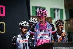 Moena, Италия 25-ое мая 2017: Профессиональный велосипедист Том Doumulin, в розовом jersey, на подписях подиума Стоковое Изображение