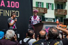 Moena, Италия 25-ое мая 2017: Профессиональный велосипедист Том Doumulin, в розовом jersey, на подписях подиума Стоковая Фотография