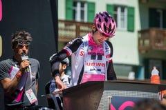 Moena, Италия 25-ое мая 2017: Профессиональный велосипедист Том Doumulin, в розовом jersey, на подписях подиума Стоковые Изображения