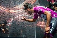 Moena, Италия 25-ое мая 2017: Профессиональный велосипедист Фернандо Gaviria, в фиолетовом Джерси, на подписях подиума Стоковые Изображения RF
