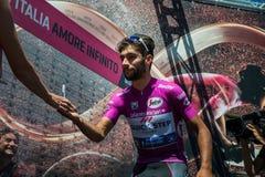 Moena, Италия 25-ое мая 2017: Профессиональный велосипедист Фернандо Gaviria, в фиолетовом Джерси, на подписях подиума Стоковое Изображение