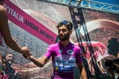 Moena, Италия 25-ое мая 2017: Профессиональный велосипедист Фернандо Gaviria, в фиолетовом Джерси, на подписях подиума Стоковое Изображение RF