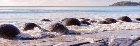 Moeraki Boulders In Beach Surf On Otago Coast. Large spherical Moeraki boulders exposed in the beach surf on the Otago coast of New Zealand stock photo
