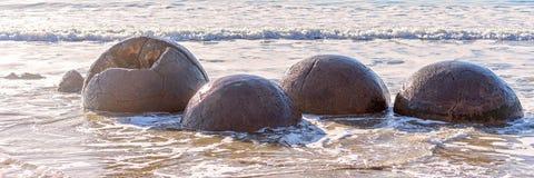 Moeraki Boulders In Beach Surf On Otago Coast. Large spherical Moeraki boulders exposed in the beach surf on the Otago cost of New Zealand stock photo
