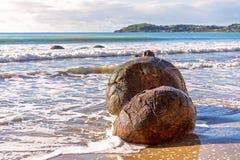 Moeraki Boulders In Beach Surf On Otago Coast. Two large spherical Moeraki boulders exposed in the beach surf on the Otago coast of New Zealand stock photo