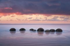 Moeraki Boulders on the Koekohe beach, Eastern coast of New Zealand. Sunset and long exposure and a dramatic dawn sky. royalty free stock photo