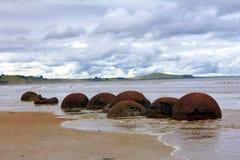Moeraki Boulders of New Zealand. Moeraki Boulders on the beach of New Zealand, perfectly round large boulders sit along the coastline Stock Images