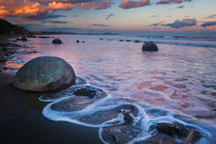 Moeraki boulders in New Zealand. Moeraki boulders at the sunset in New Zealand. Volcanic landscape on the coast line with water and ocean in the background royalty free stock images