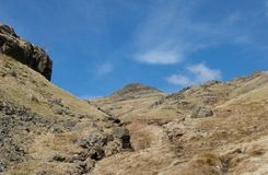 Moerassige vallei met bergpieken, rotsen, stroom en voetpadmeerdistrict stock afbeelding
