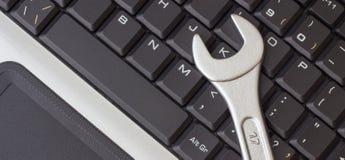 Moersleutel op het laptop toetsenbord, het concept het herstellen van machines, close-up stock afbeelding
