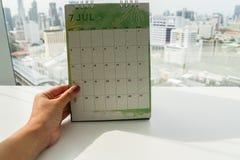 Mofa aislada del control de la mujer encima del calendario creativo de julio del diseño Fotos de archivo