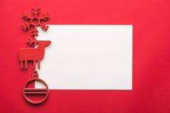 Mofa de la tarjeta de felicitación encima de la plantilla con las decoraciones de la Navidad en fondo de madera Visión desde arri Foto de archivo