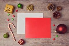 Mofa de la tarjeta de felicitación encima de la plantilla con las decoraciones de la Navidad en fondo de madera Visión desde arri Fotos de archivo