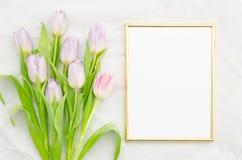 Mofa de moda para arriba con los tulipanes rosados y el marco vacío de oro Endecha plana, visión superior Foto de archivo