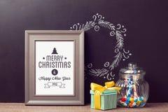 Mofa del cartel de la Navidad encima de la plantilla con el tarro del caramelo sobre fondo de la pizarra Imágenes de archivo libres de regalías