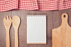 Mofa del cuaderno encima de la plantilla con los utensilios y el mantel de la cocina Visión desde arriba Fotos de archivo