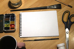 Mofa del cuaderno para arriba para las ilustraciones con las pinturas de la acuarela, paleta, vidrio de agua y brochas Herramient Imagen de archivo libre de regalías