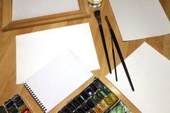 Mofa del cuaderno para arriba para las ilustraciones con las pinturas de la acuarela, paleta, vidrio de agua y brochas Herramient Fotografía de archivo libre de regalías