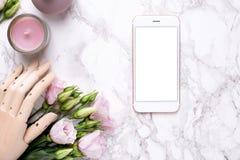 Mofa del teléfono móvil para arriba y mano de madera con las flores rosadas en el fondo de mármol foto de archivo