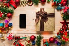 Mofa elegante del teléfono ascendente y caja de regalo con las decoraciones de la Navidad Foto de archivo libre de regalías