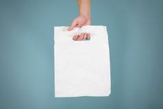 Mofa en blanco de la bolsa de plástico de las demostraciones de la mano para arriba aislada Polye blanco vacío fotografía de archivo libre de regalías