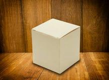 Mofa en blanco de la caja blanca para arriba en el fondo de madera Imagen de archivo libre de regalías