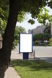 Mofa en blanco para arriba de la cartelera vertical del cartel de la calle en fondo de la ciudad foto de archivo libre de regalías