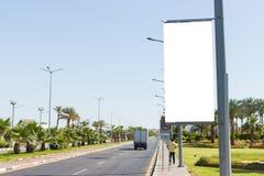 Mofa en blanco para arriba de la cartelera vertical del cartel de la calle en fondo de la ciudad del summmer foto de archivo libre de regalías