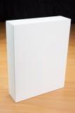 Mofa encima de la caja blanca en el fondo de madera Foto de archivo