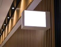 Mofa encima de la caja de luz de la señalización en logotipo de madera de la tienda de la pared Fotos de archivo libres de regalías