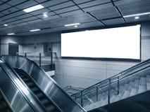 Mofa encima de la cartelera en la estación de metro con la escalera móvil fotos de archivo