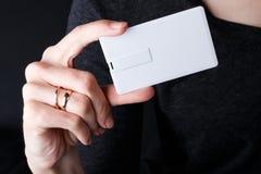 Mofa para arriba mujer que sostiene la tarjeta de memoria Flash blanca del usb de la tarjeta imagenes de archivo