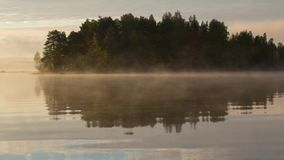 Mog creeping along the surface of the lake at sunrise timelapse. Finland stock footage
