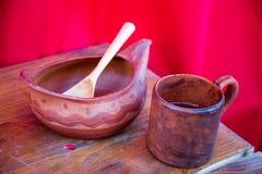 Mogano di legno del cucchiaio della tazza della ciotola dipinto con un modello semplice su un fondo rosso Fuoco selettivo fotografie stock libere da diritti