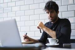 Mogen ägare av en affär i ett svart skjortasammanträde i coworking utrymme med den fria internet 4G Royaltyfri Foto