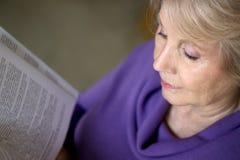 Mogen äldre kvinna som läser en bok Arkivbilder