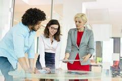 Mogen affärskvinna med kollegor som i regeringsställning diskuterar över projekt på tabellen arkivfoton
