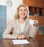 Mogen affärskvinna med kopp te på tabellen Arkivfoton